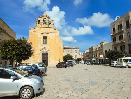 Favignana, Sicily, Italy - March 10, 2015: People and cars near the church  of the Piazza Matrice