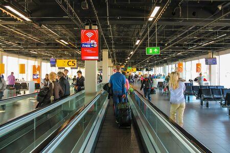 Amsterdam Schiphol, Netherlands - April 18, 2015: Interior of Amsterdam Airport Schiphol. Passengers on a long horizontal escalator Editorial