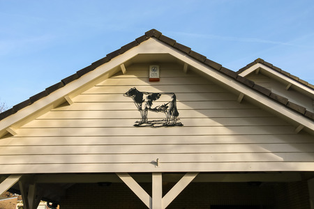 house gable: Meerkerk, municipality Zederik, Netherlands - April 13, 2015: Metal bas-relief depicting a cow decorated gable house in Meerkerk, Netherlands