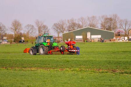 field work: Meerkerk, municipality Zederik, Netherlands - April 13, 2015: Tractor operator on the tractor carries out field work