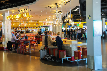 Amsterdam Schiphol, Netherlands - April 18, 2015: Passengers relax in the cafe Comunal at the airport Amsterdam Schiphol, Netherlands