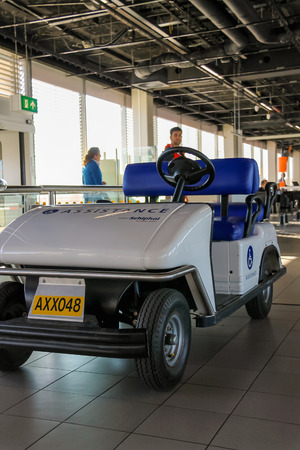 schiphol: Amsterdam Schiphol, Netherlands - April 18, 2015: Interior of Amsterdam Airport Schiphol. Passengers near the electric vehicle for transporting people with disabilities