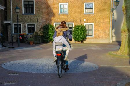 dutch girl: Meerkerk, municipality Zederik, Netherlands - April 13, 2015: The woman and little girl riding a bicycle in the Dutch city Meerkerk, Netherlands Editorial