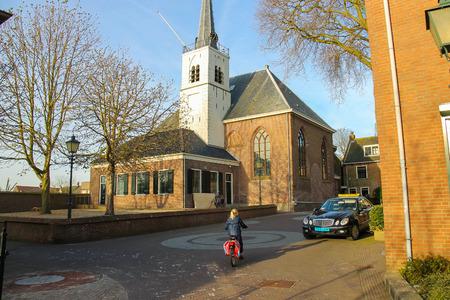 dutch girl: Meerkerk, municipality Zederik, Netherlands - April 13, 2015: Little girl riding a bicycle in the Dutch city Meerkerk, Netherlands