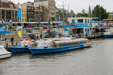cruiseboat: Amsterdam, Netherlands - June 20, 2015: People on the dock landing on river cruise ships, Amsterdam, Netherlands Editorial
