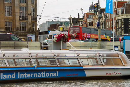 Amsterdam, Netherlands - June 20, 2015: Excursion ships are near the pier on the waterfront in Amsterdam