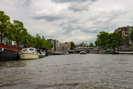 Amsterdam, Netherlands - June 20, 2015: Boats on a canal in Amsterdam. Netherlands Editorial