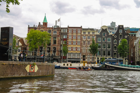 cruiseboat: Amsterdam, Netherlands - June 20, 2015: People on the waterfront of canal in Amsterdam