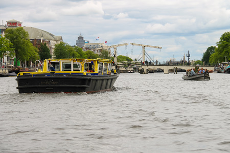 Amsterdam, Netherlands - June 20, 2015: People in the boat on tours of the canals of Amsterdam