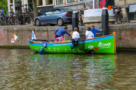 Amsterdam, Netherlands - June 20, 2015: Children in boat publicizing ecological way of life on the canal in Amsterdam.