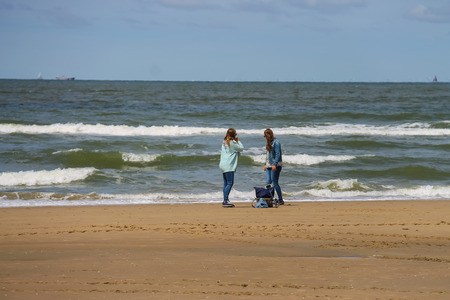 bordered: Zandvoort, the Netherlands- June 20, 2015: Two young women on sandy beach near North sea. Zandvoort aan Zee is a main sea resort and touristic center with a long sandy beach bordered by coastal dunes. Editorial