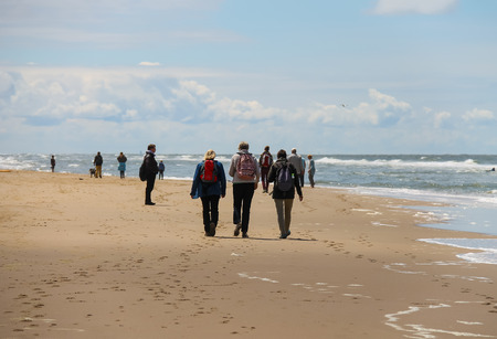 bordered: Zandvoort, the Netherlands- June 20, 2015: Tourists are walking along the sea line. Zandvoort aan Zee is a main sea resort and touristic center with a long sandy beach bordered by coastal dunes. Editorial