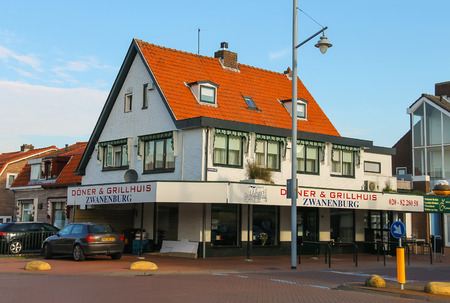 autos: Zwanenburg, the Netherlands - Oct 03, 2015: Donuts and Grill House and autos near it. Zwanenburg is a small picturesque town in the Dutch province of North Holland.