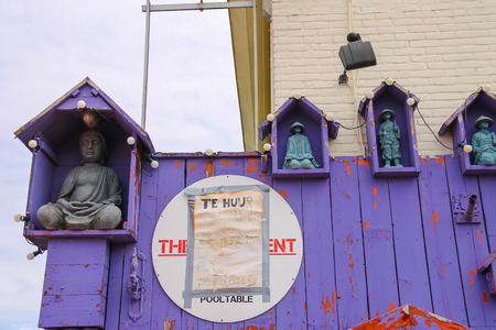 inform information: Zandvoort, the Netherlands - June 20, 2015: Statues of Buddha and Chinese sages decorating wooden wall. Zandvoort aan Zee is a major sea resort and tourist center of North sea