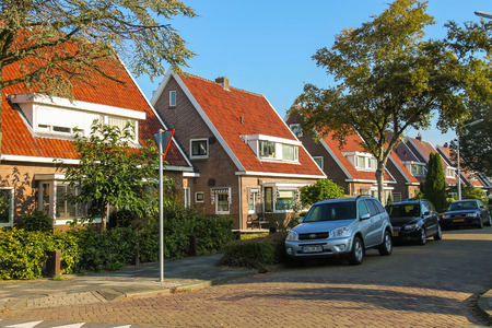 autos: Zwanenburg, the Netherlands - Oct 03, 2015: Picturesque residential houses and parked autos in small town Zwanenburg in the Dutch province of North Holland