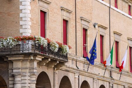 cavour: Facade of Rimini City Hall with flags and flowers on Cavour square in Rimini, Italy