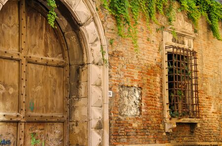 barred: Rimini, Italy - August 16, 2014: Old wooden door and barred window of ancient building in centre of Rimini Editorial