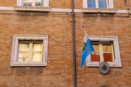 consulate: Rimini, Italy - August 16, 2014: National flag over the entrance to the consulate of the Republic of San Marino in centre of Rimini.