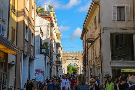 augustus: Rimini, Italy - August 16, 2014: Tourists walking from Tre Martiri square (Piazza Tre Martiri) to Arch of Augustus (Arco di Augusto).