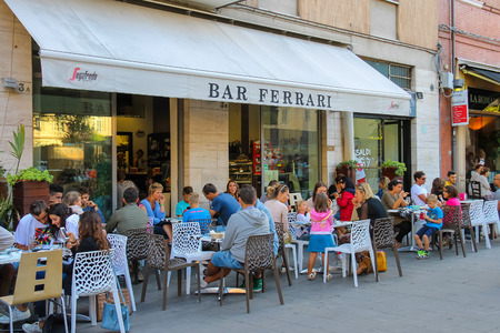 ferrari: Rimini, Italy - August 16, 2014: People sitting in Ferrari bar on Luigi Ferrari square (Piazza Luigi Ferrari) Editorial