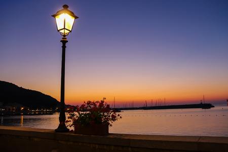 lighted: Lighted lantern on coast of the Tyrrhenian Sea on the sunset. Elba Island, Italy Stock Photo