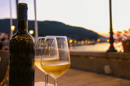 Fles van witte wijn en twee glazen op tafel restaurant op zonsondergang Stockfoto