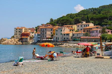 tyrrhenian: Marciana Marina, Italy - July 01, 2015: People taking a sunbath on the coast of the Tyrrhenian Sea, Elba Island. Marciana Marina is  one of the most important towns of Elba Island in region of Tuscany, Italy