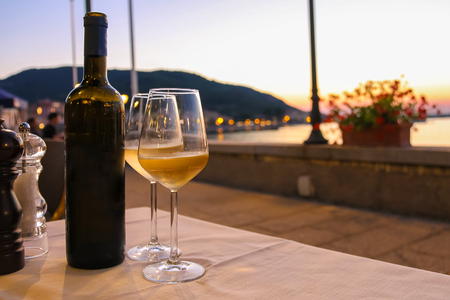 alcoholic beverage: Bottle of white wine and two glasses on the restaurant table on sunset