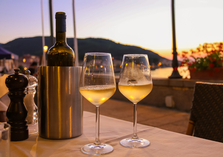 close up view: Bottle of white wine and two glasses on the restaurant table on sunset