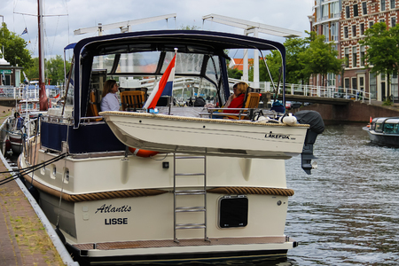 berth: Haarlem, the Netherlands - June 20, 2015: People resting on the yacht board. Haarlem is the capital of the province of North Holland and popular tourist centre