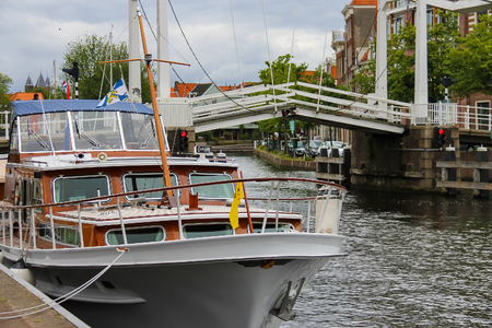 berth: Haarlem, the Netherlands - June 20, 2015: Anchored yachts near the drawbridge. Haarlem is the capital of the province of North Holland and popular tourist centre