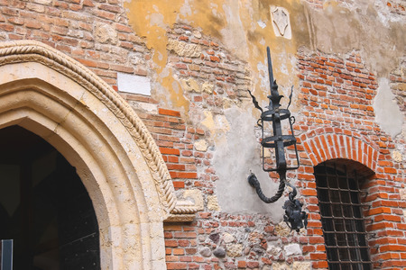 luminaire: Medieval luminaire on old brick wall of a house