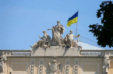 architectural studies: The upper part of Ivan Franko National University main building with National Flag of Ukraine.  Allegorical sculpture composition Galicia, Vistula and Dniester. Lviv, Ukraine