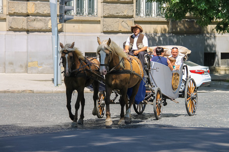 brougham: Lviv, Ukraine - July 5, 2014: Tourist carriage with people on the streets in historical city center