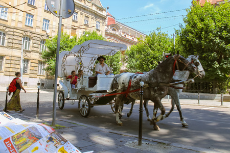 brougham: Lviv, Ukraine - July 5, 2014: Tourist brougham with people on the streets in historical city center Editorial
