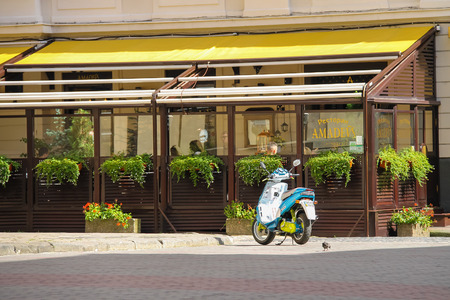 amadeus: Lviv, Ukraine - July 5, 2014: Parked moped near outdoor terrace of restaurant Amadeus in historic city center Editorial