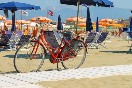 viareggio: Viareggio, Italy - June 28, 2015: Parked bicycle on the beach. Viareggio is the famous resort on the coast of the Ligurian Sea Editorial