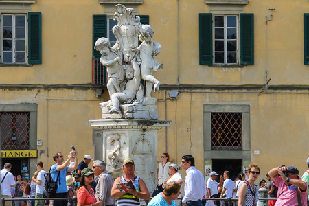 angels fountain: Pisa, Italy - June 29, 2015: Tourists near the fountain with angels on Piazza dei Miracoli. Province Pisa, Tuscany region of Italy