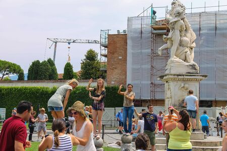 angels fountain: Pisa, Italy - June 29, 2015: Tourists near the fountain with angels on Piazza del Duomo. Province Pisa, Tuscany region of Italy Editorial