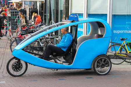 rickshaw: Amsterdam, the Netherlands -October 03, 2015: Bicycle taxi cyclist waiting for passengers in historic city centre Editorial