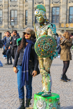 Amsterdam, the Netherlands -October 03, 2015: Young woman near the human statue street performer on Dam Square in historic city centre