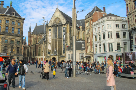 dam square: Amsterdam, the Netherlands -October 03, 2015: Tourists walking on Dam Square in historic city centre Editorial
