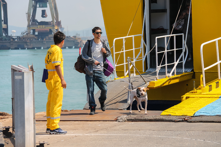 docker: Piombino, Italy - June 30, 2015: Man with dog coming out of the ferry boat Corsica Express in the seaport