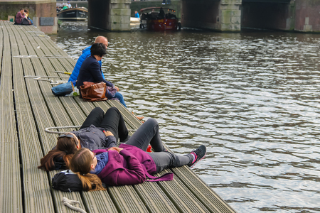 berth: Amsterdam, the Netherlands - October 03, 2015: People resting at berth near the water