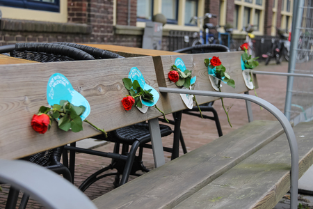 romantic places: Utrecht, the Netherlands - February 13, 2016: Red roses on the wooden bench in historic city centre Editorial