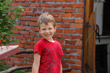Laughing beautiful little boy standing in front of old brick house