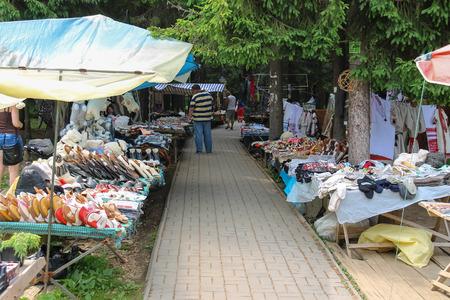Schodnica, Ukraine - June 30, 2014: People walking between trade stalls with ukrainian souvenirs