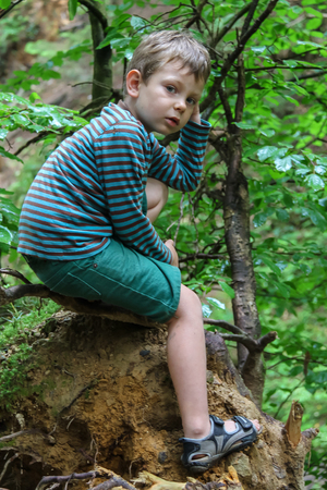 grub: Small boy in striped sweater and shorts in summer forest park Stock Photo