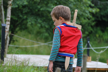 Boy with wooden sword in summer forest park Stock Photo