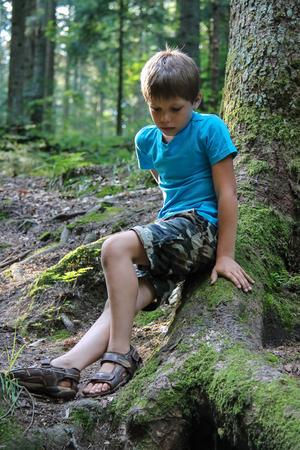 夏の森に座っているハンサムな少年
